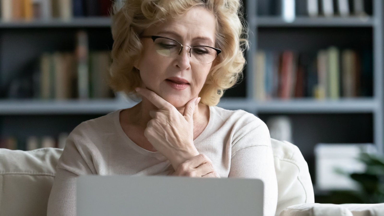 Senior Woman sitting at home on her sofa looking contemplative while staring at her laptop