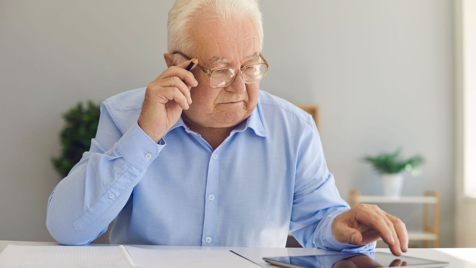 Senior man looking at his tablet making notes as if researching online