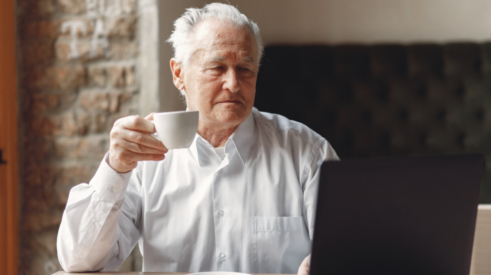 Senior man with a skeptical look on his face looking at his laptop holding a white ceramic mug of coffee