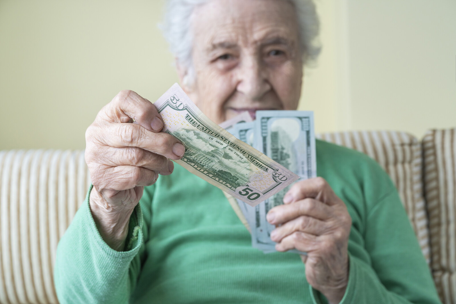 Senior woman in green sweater handing a fifty dollar to someone holding cash in the other hand