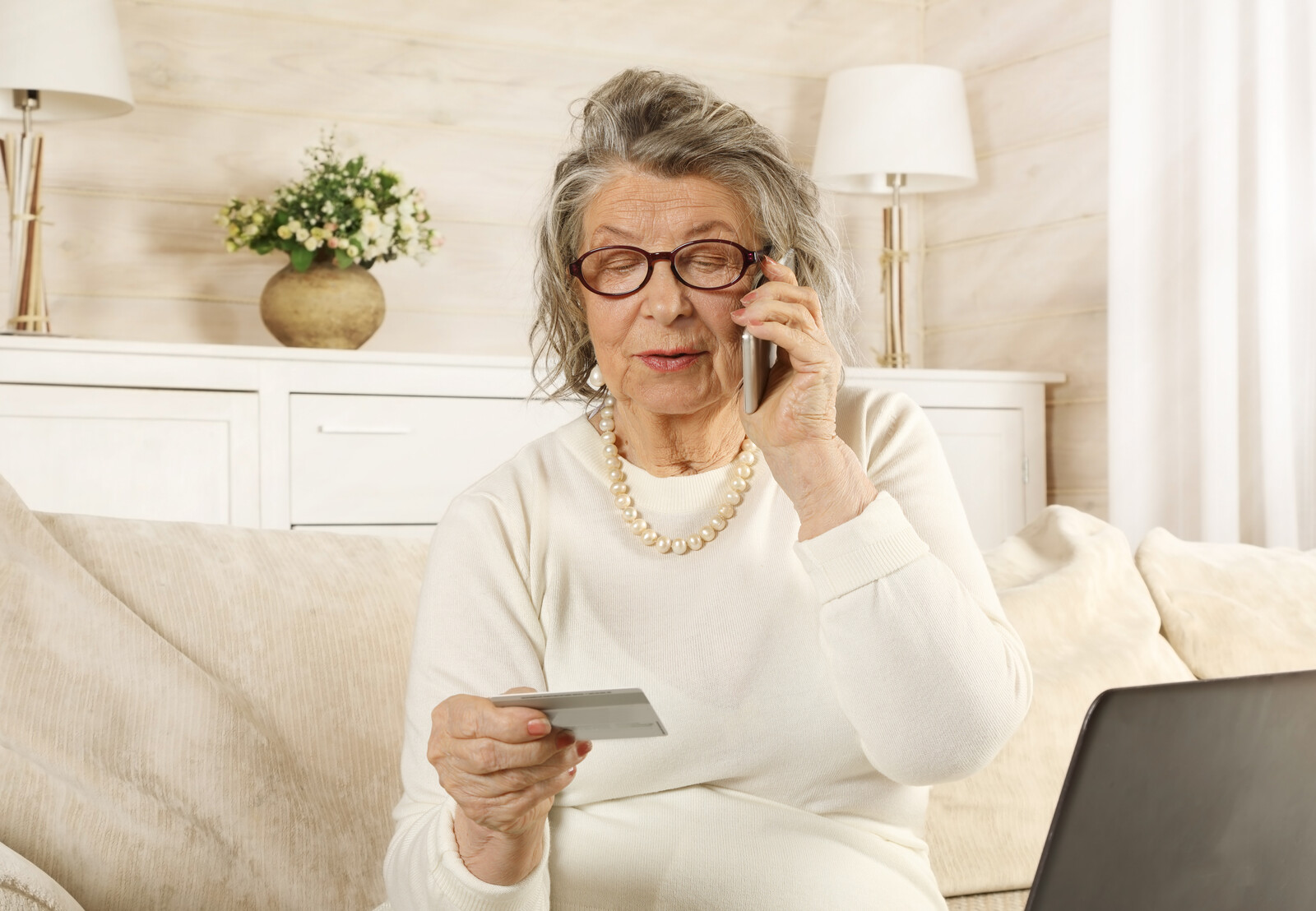 Senior woman on couch talking on the cell making a payment