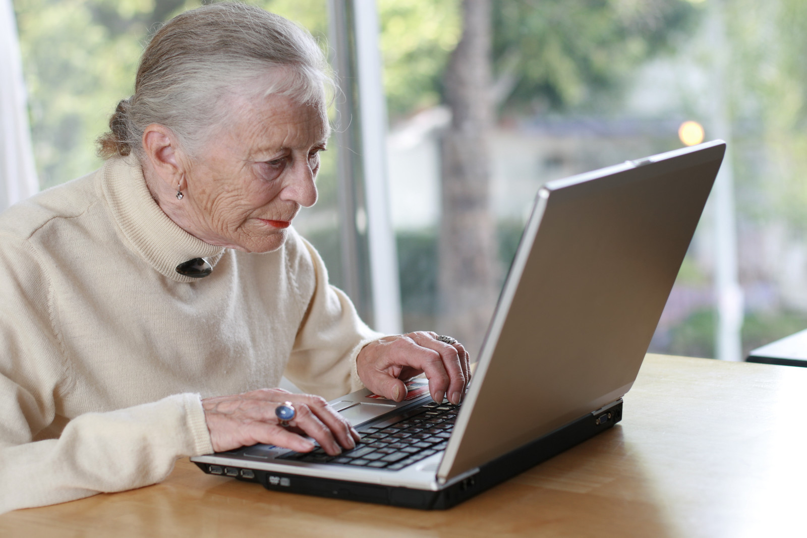 Senior woman on her computer at the kitchen table representing her taking the time to learn about jury duty scams