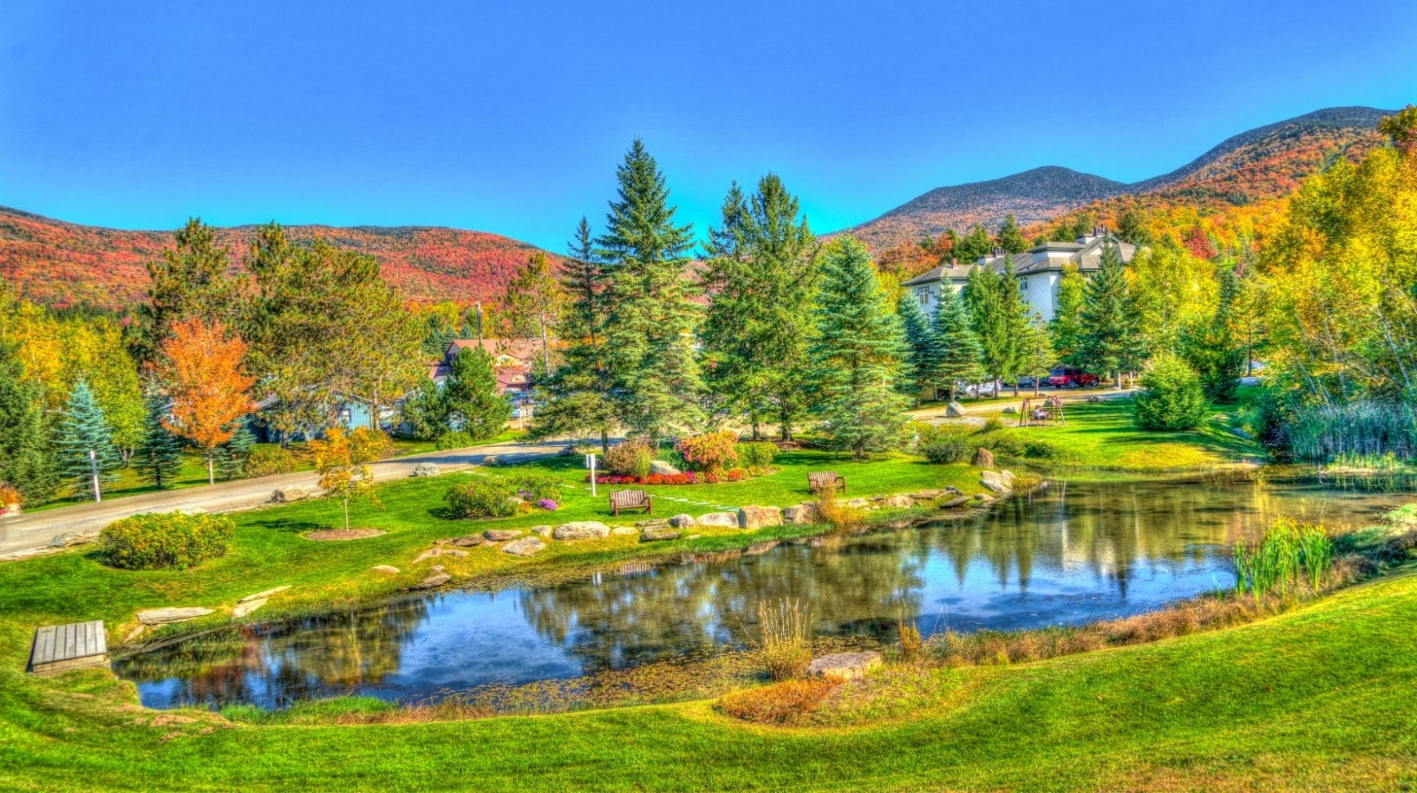 Top places to retire in Vermont -Fall with vibrant colors, reflections on the pond, blue skies, and hills dotted with autumn colors. Houses are tucked amongst the trees