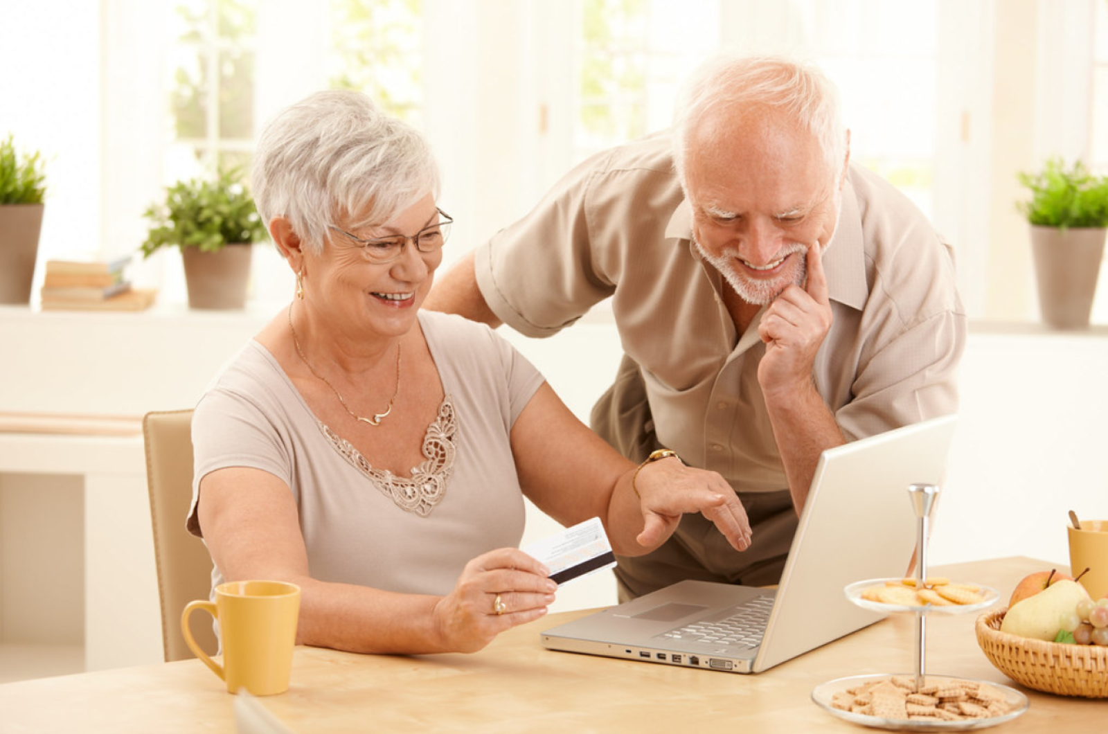 Online Shopping Scams - Senior couple sitting at breakfast table on a sunny day at home shopping online