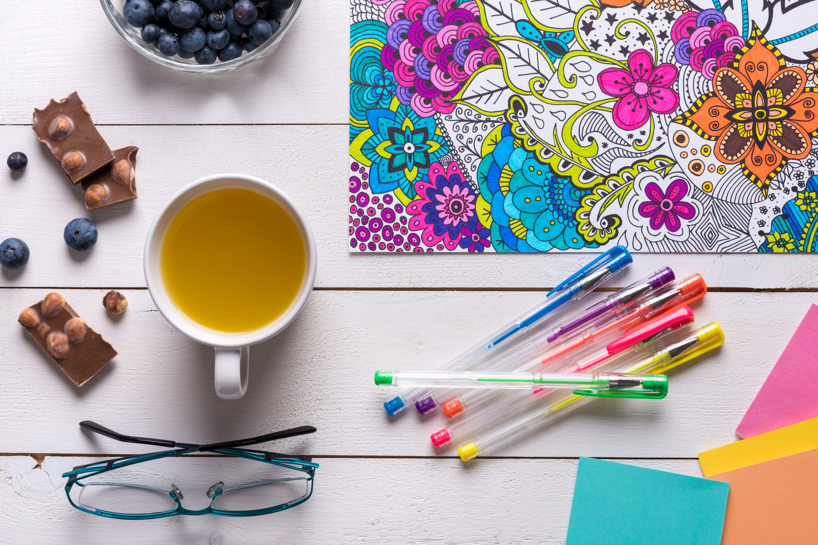 5 Benefits for Why Every Senior Should Start Coloring- Adult coloring book page filled with flowers partially colored in  with gel pens, candy, blueberries, tea and reading glasses sitting on the table nearby