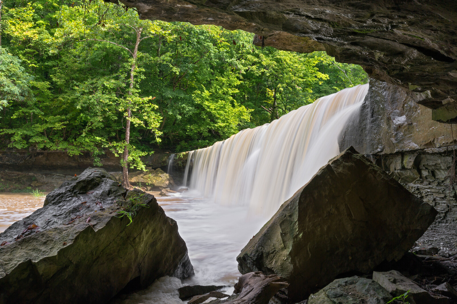 Sunny day at Anderson falls with an overhanging rock formation with greenery on the other side of the falls, near columbus, Indiana