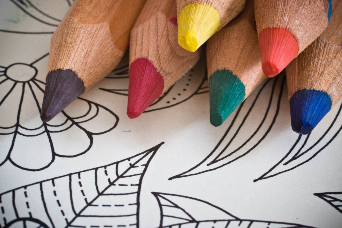 6 colored pencils stacked on each other sitting on an adult coloring sheet with flowers