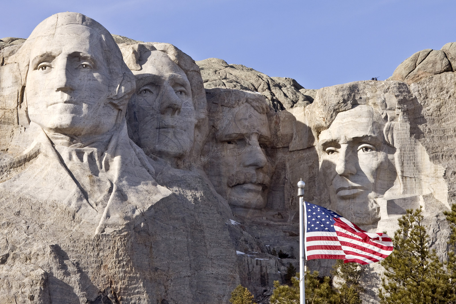 Top 5 Places To Retire in South Dakota - Mount rushmore south dakota black hills on a sunny day with the American Flag flying in front