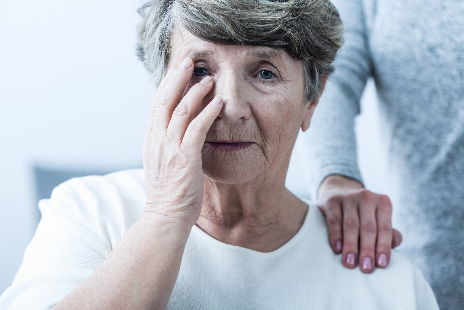 Older woman looking confused with her hand to her head sitting with a friendly hand on her shoulder