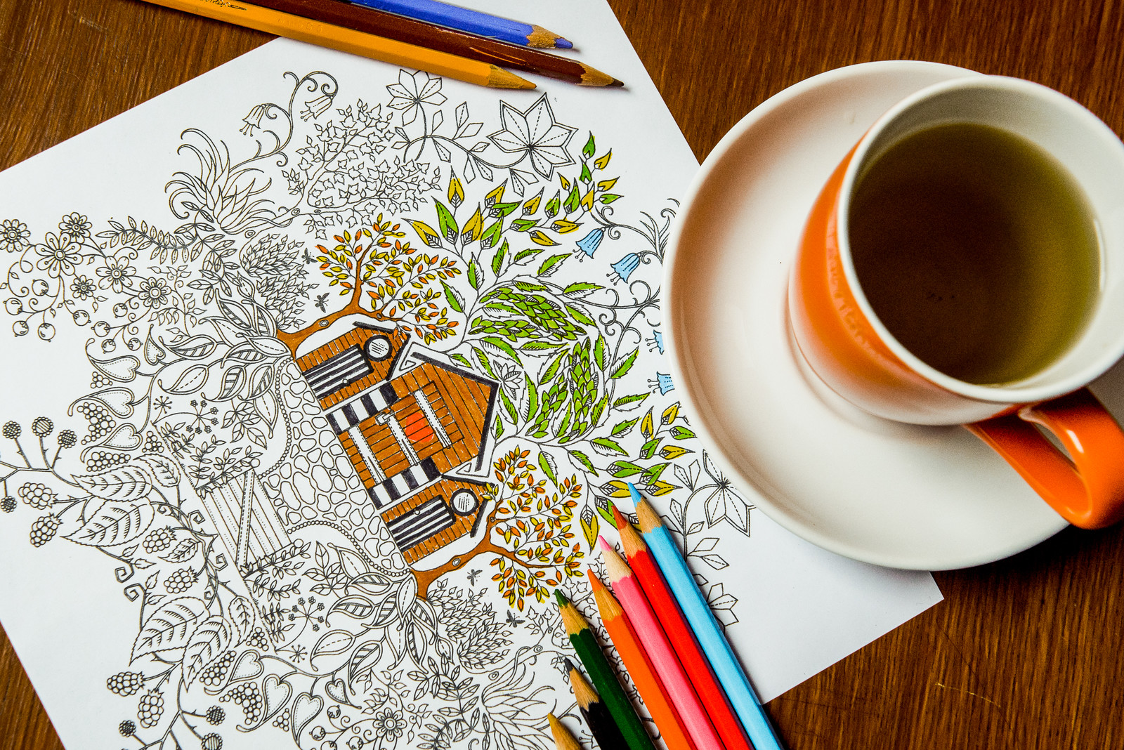 Partially colored adult coloring page with an image of three tiny houses surrounded by leaves and flowers. A cup of tea sitting on the corner of the page and colored pencils sitting on the edge of the sheet