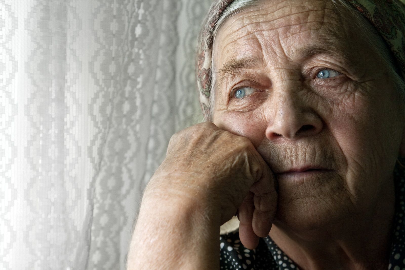 Depressed looking woman looking sad out the window