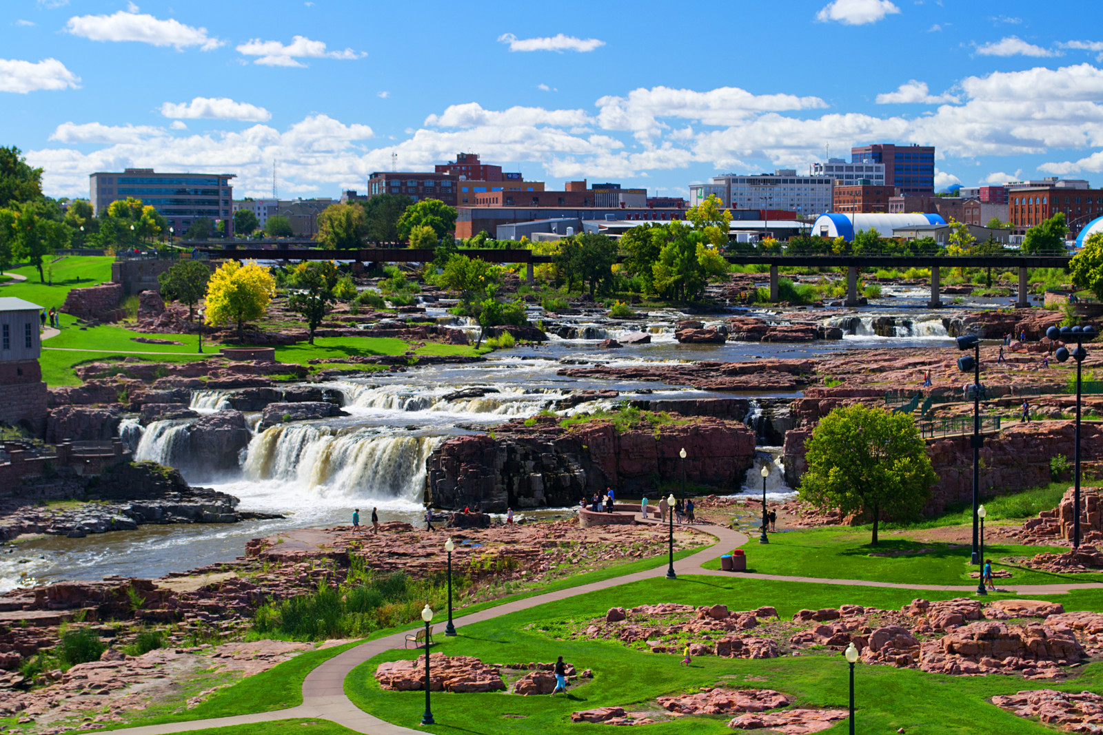 Sioux Falls at Falls park with walkways, green grass, and street lights lining the paths, with the city in the backdrop with blue skies
