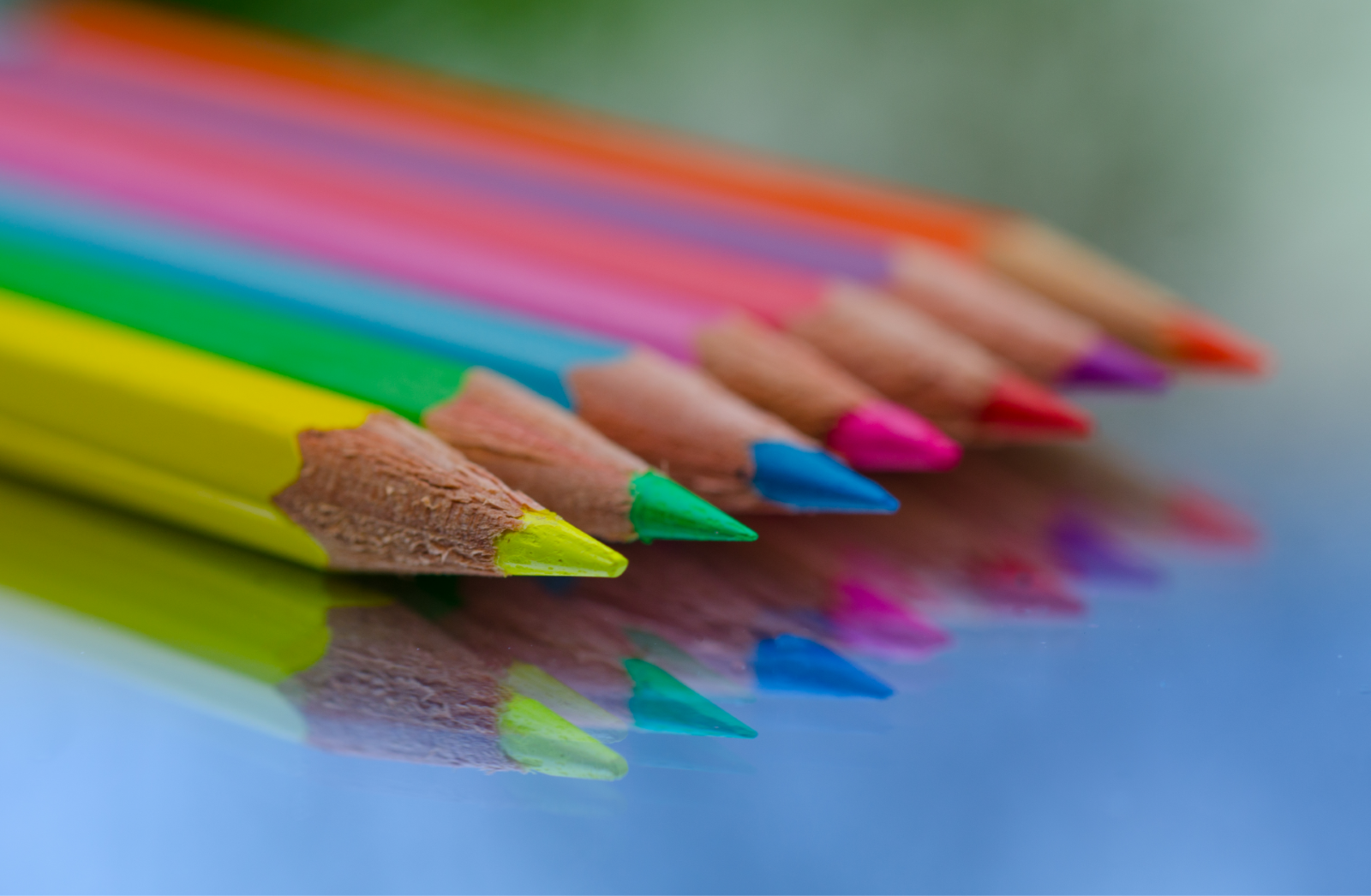 Seven colored pencils  lined up on a reflective surface