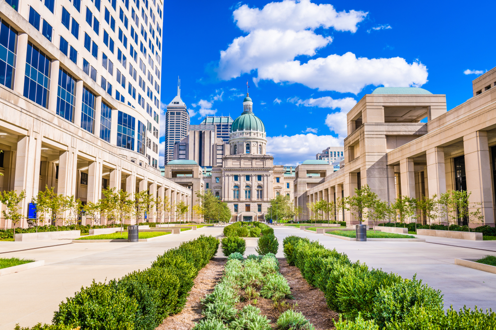 Looking down an avenue in the capital building in Indianapolis Indiana, with greenery down the middle and a blue sky