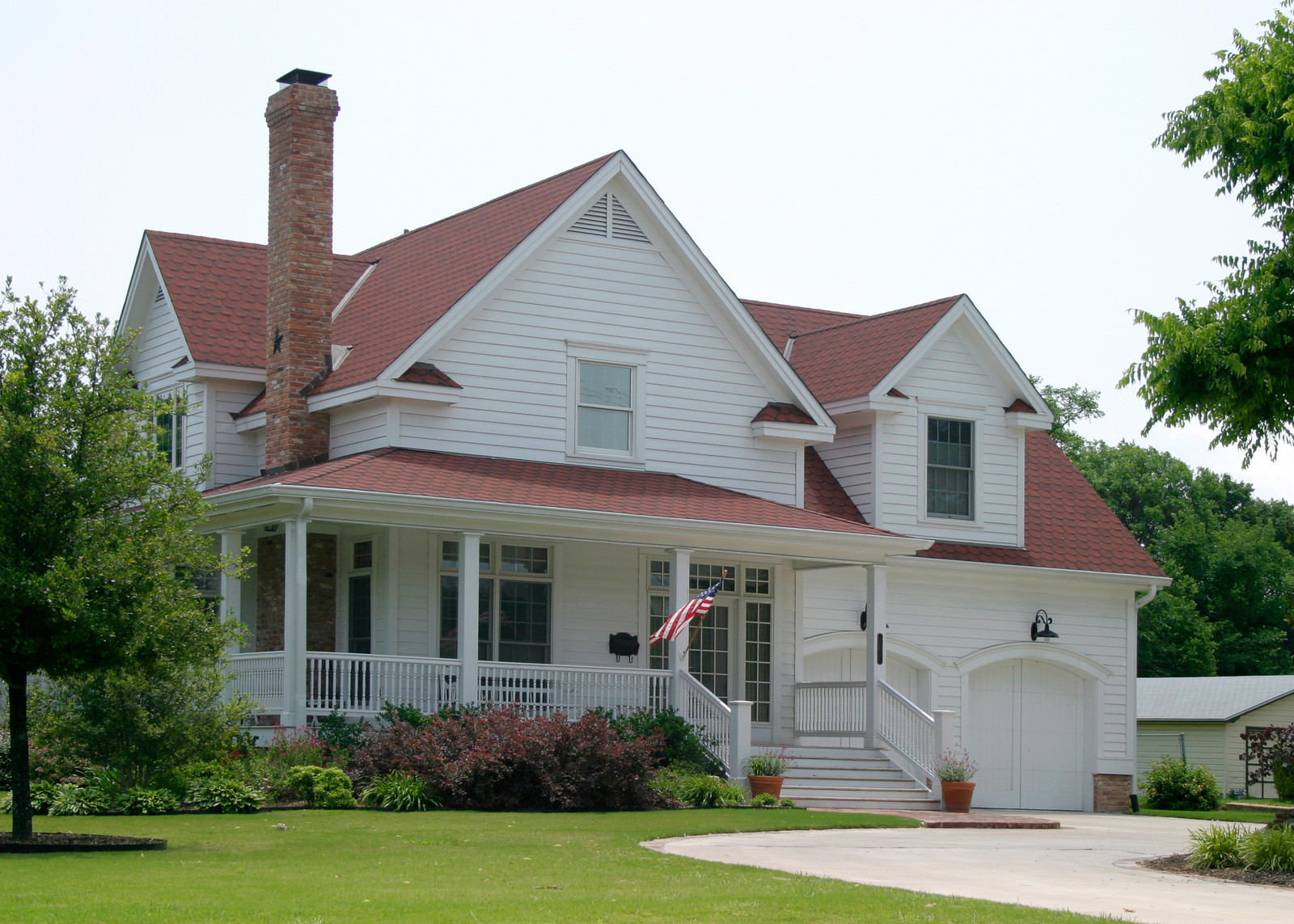 White house with dark red shingles and brick chimney. Large wrap around front porch and green lawn with shrubs and trees