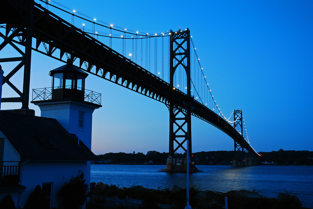 A lighthouse by the Bristol Mount Hope Bridge in Rhode Island where the sky and water are dark blue