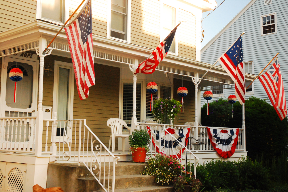 A patriotic house in Bristol Rhode Island where there are four flags flying, American banners on the railing and other decorations