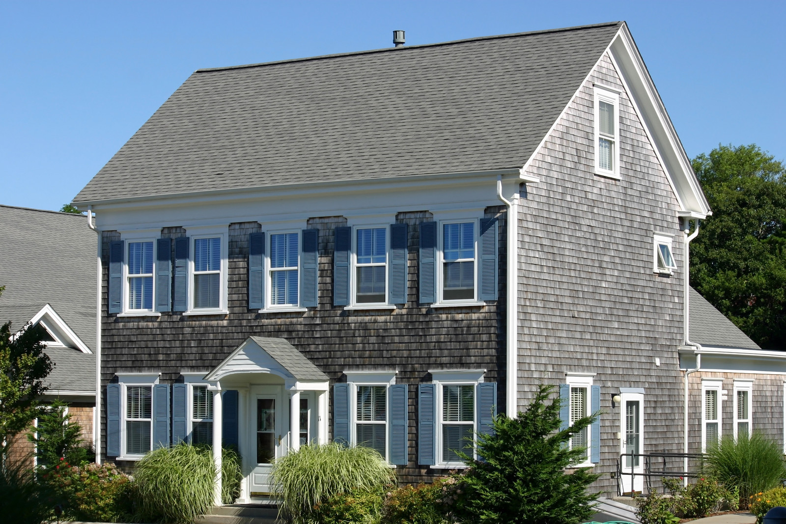 Gray cape cod house with wood shake siding with blue skies with shrubs and decorative grass throughout the yard