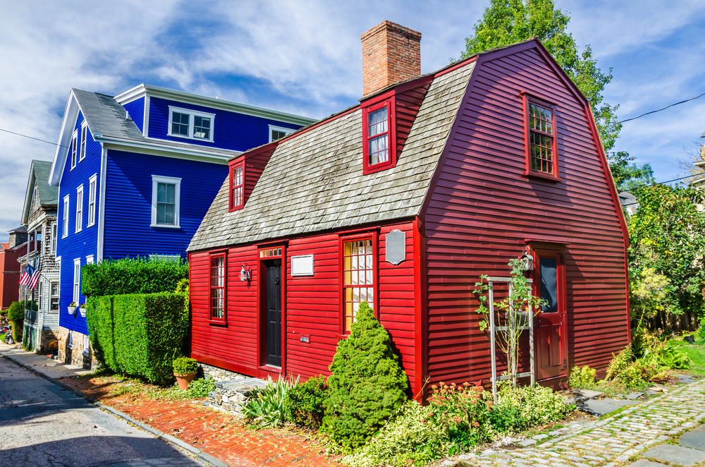 A bright red wooden house in Newport Rhode Island with a blue house behind it