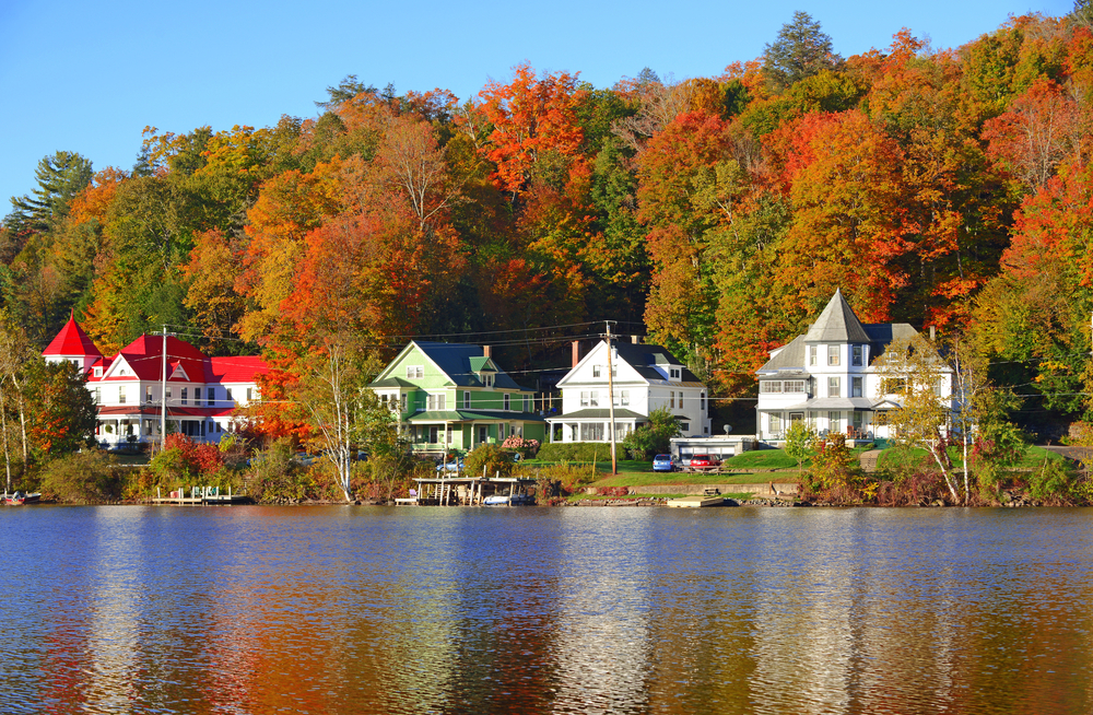 Buildings in Saranac Lake against orange trees in fall and right next to the lake itself