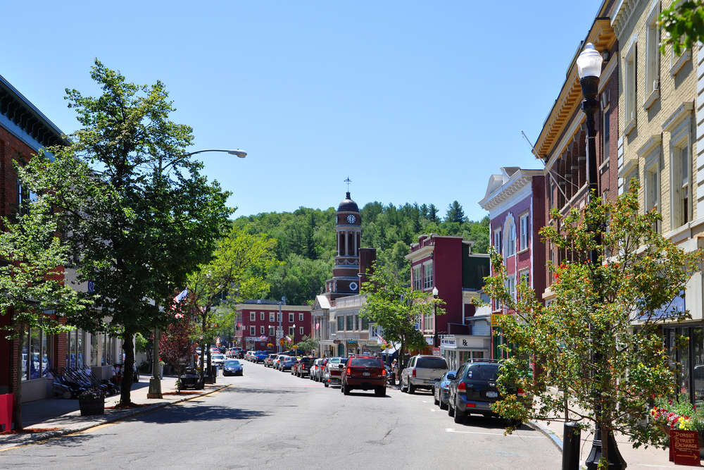 Cars down the main street of Saranac Lake on a sunny day where the sky is blue