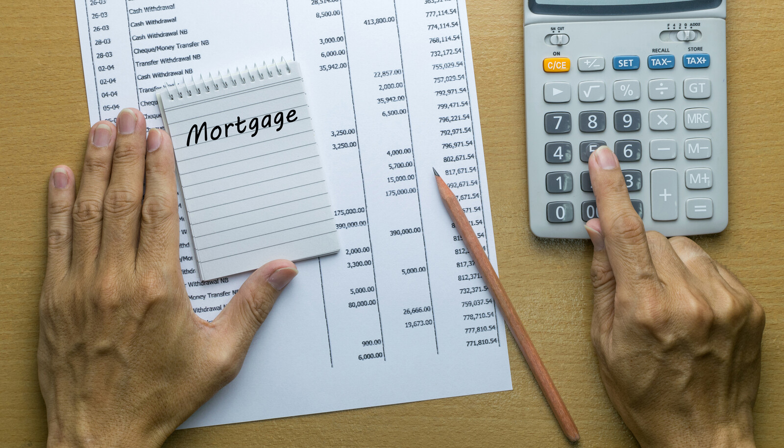 Man planning bi-monthly mortgage payment at a wood table with a calculator, notepad, pencil, and past mortgage payment information