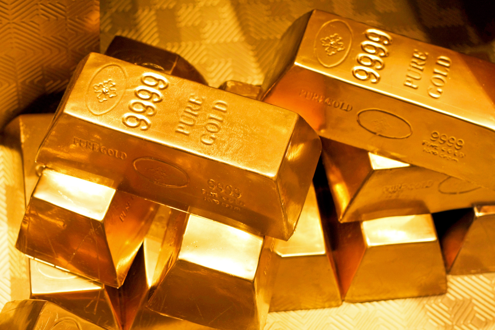 Photo of a pile of pure gold bars all stamped with 9999 pure gold