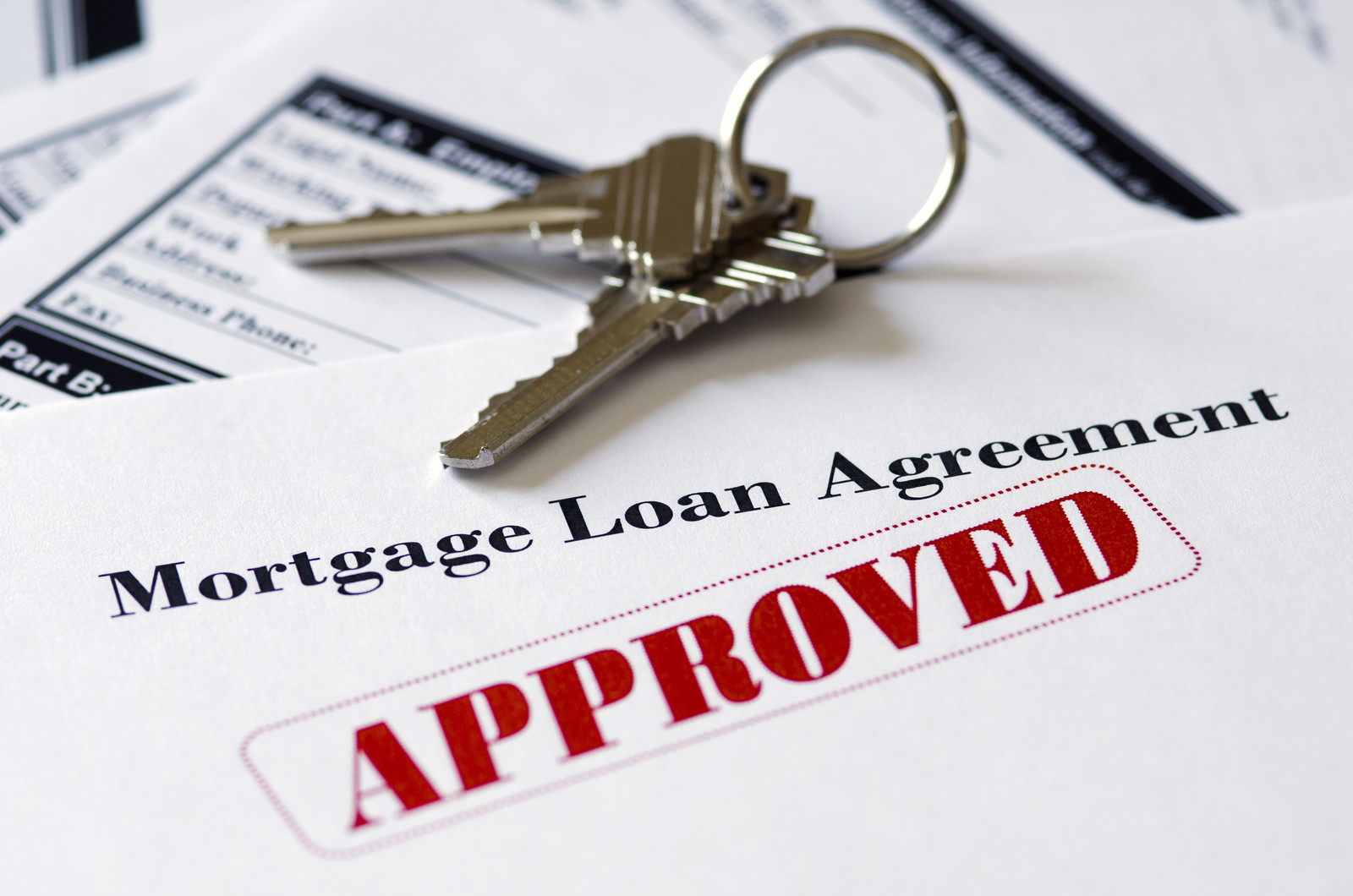 REAL ESTATE MORTGAGE AGREEMENT WITH A RED STAMP STATING APPROVED WITH A SET OF HOUSE KEYS SITTING ON TOP