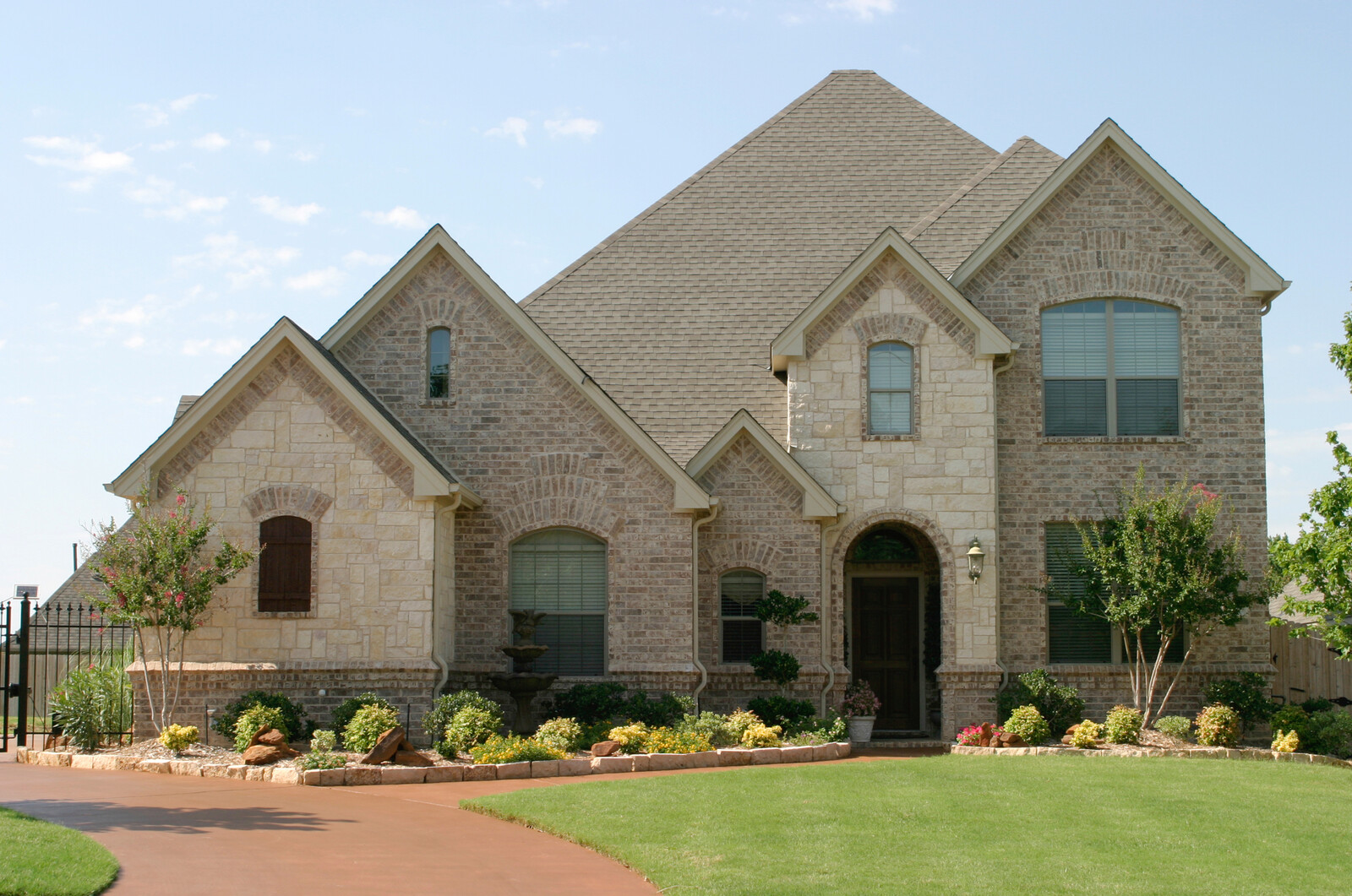 Taupe brick house with green yard and shrubbery around the base of the house and black iron fence