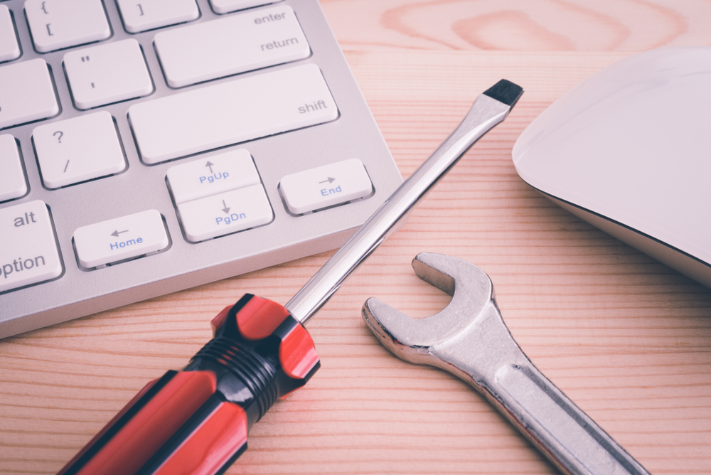 A screwdriver and a wrench by a computer, highlighting the idea of homeowner insurance warrenty