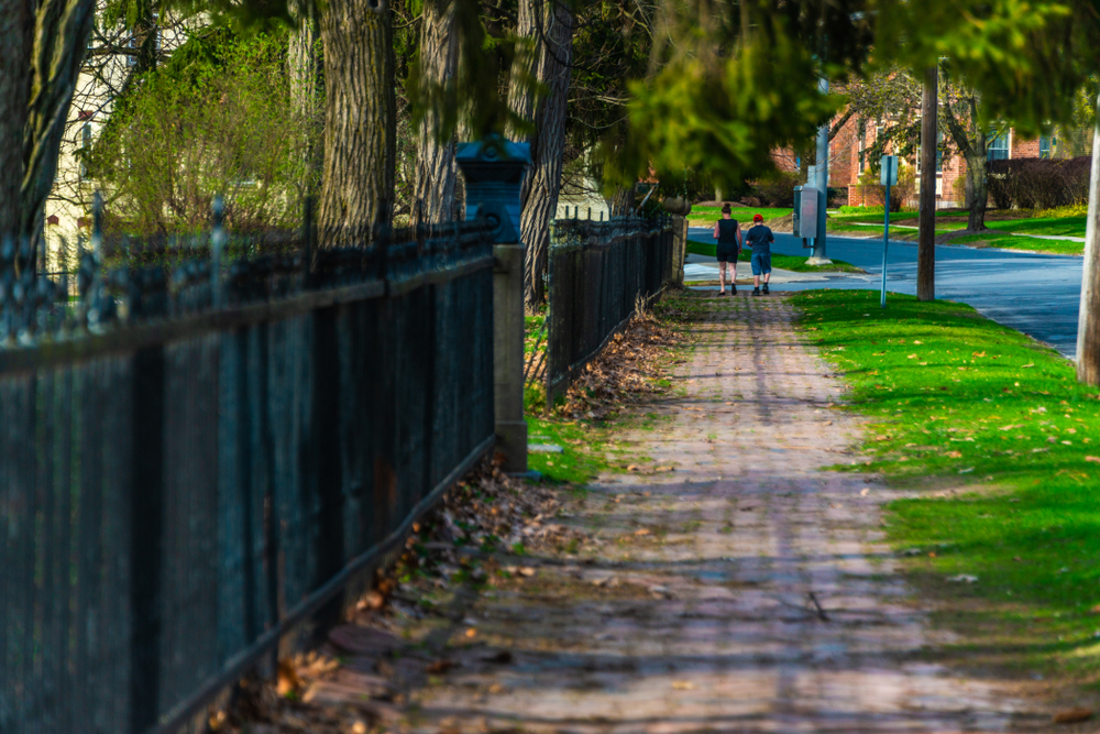 Two people walking down the sidewalk in Saratoga Springs New York, next to a fence and trees on one side and bright green grass on the other
