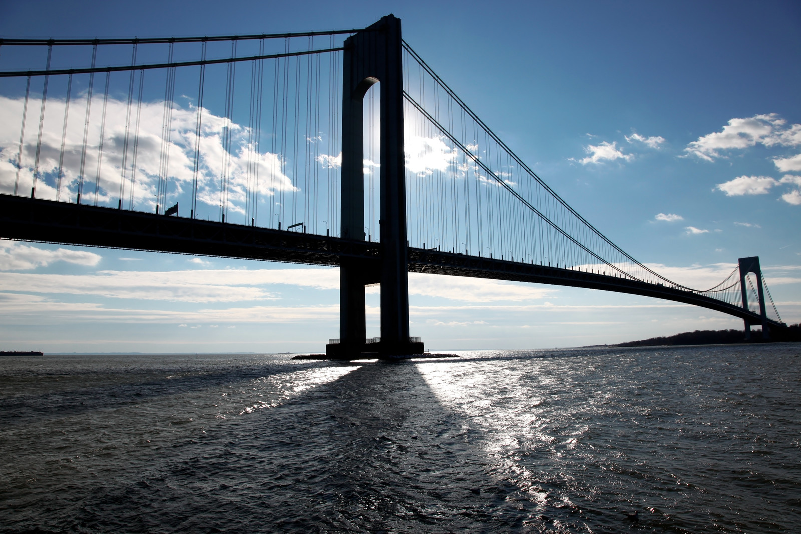 Verrazano  bridge from Brooklyn to Staten Island on a bright day with blue skies and white clouds