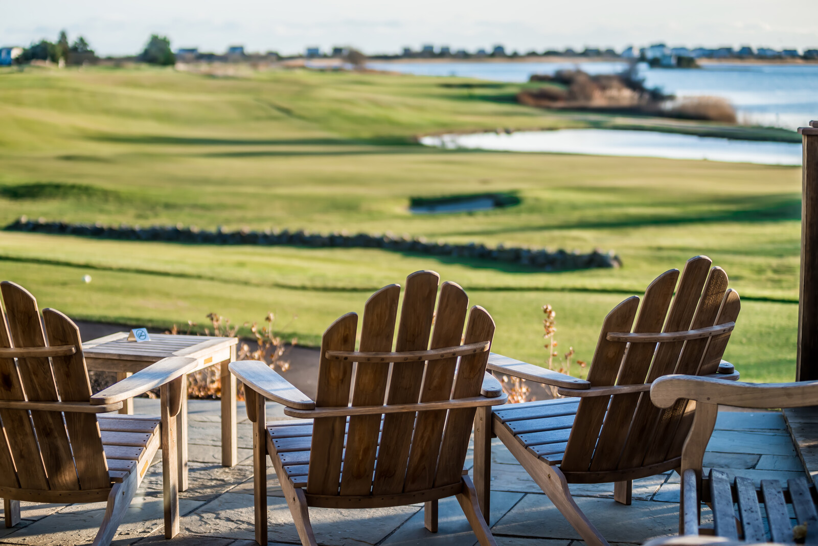 Sunny day at Weekapaug golf club from the patio with three deck chairs and small table overlooking the greens and sand trap