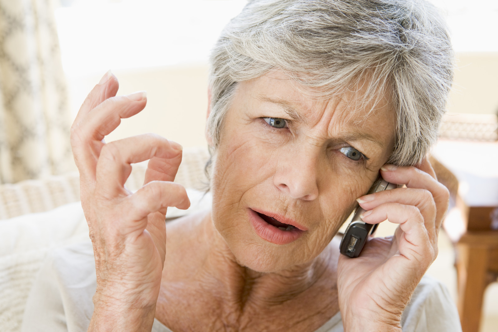 Senior woman on cell phone looking upset - representing a robocall for a fake past due utility bill