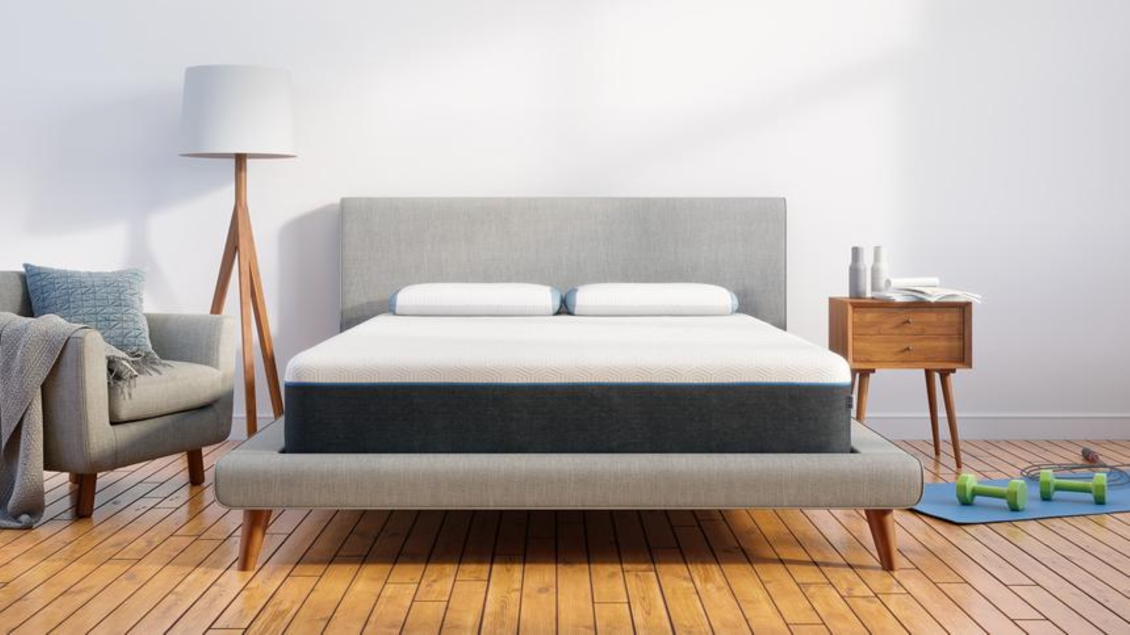 BEAR Mattress on a gray bedframe sitting on a woodfloor with a gray chair and floor lamp on the left and a night stand and workout equipment on the right