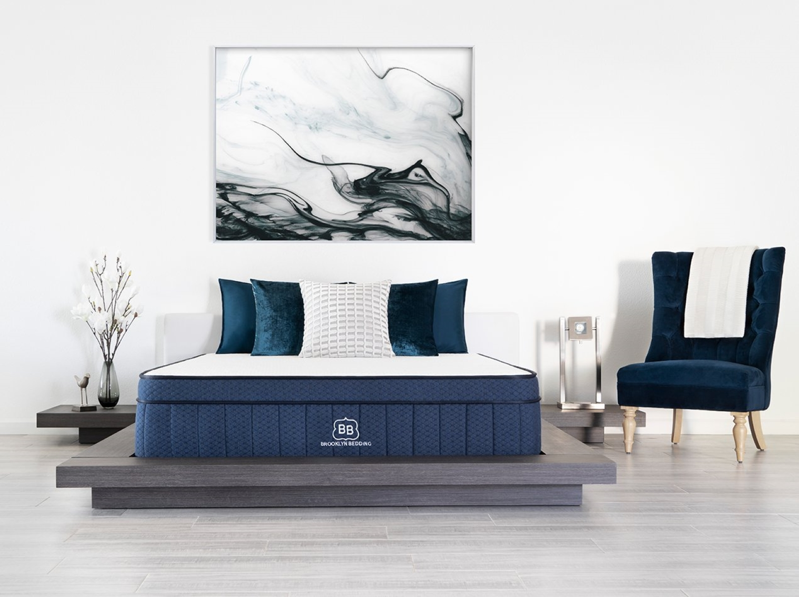 Blue based brooklyn bedding mattress in a gray bed frame with two night stands on the side of the bed with gray flooring and a blue chair on the side with a painting hanging over the bed