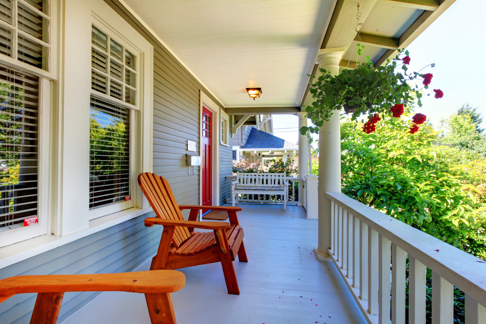 Front porch of the grey house with white railings with hanging red geraniums, Adirondack chair and white bench with shrubs in the front