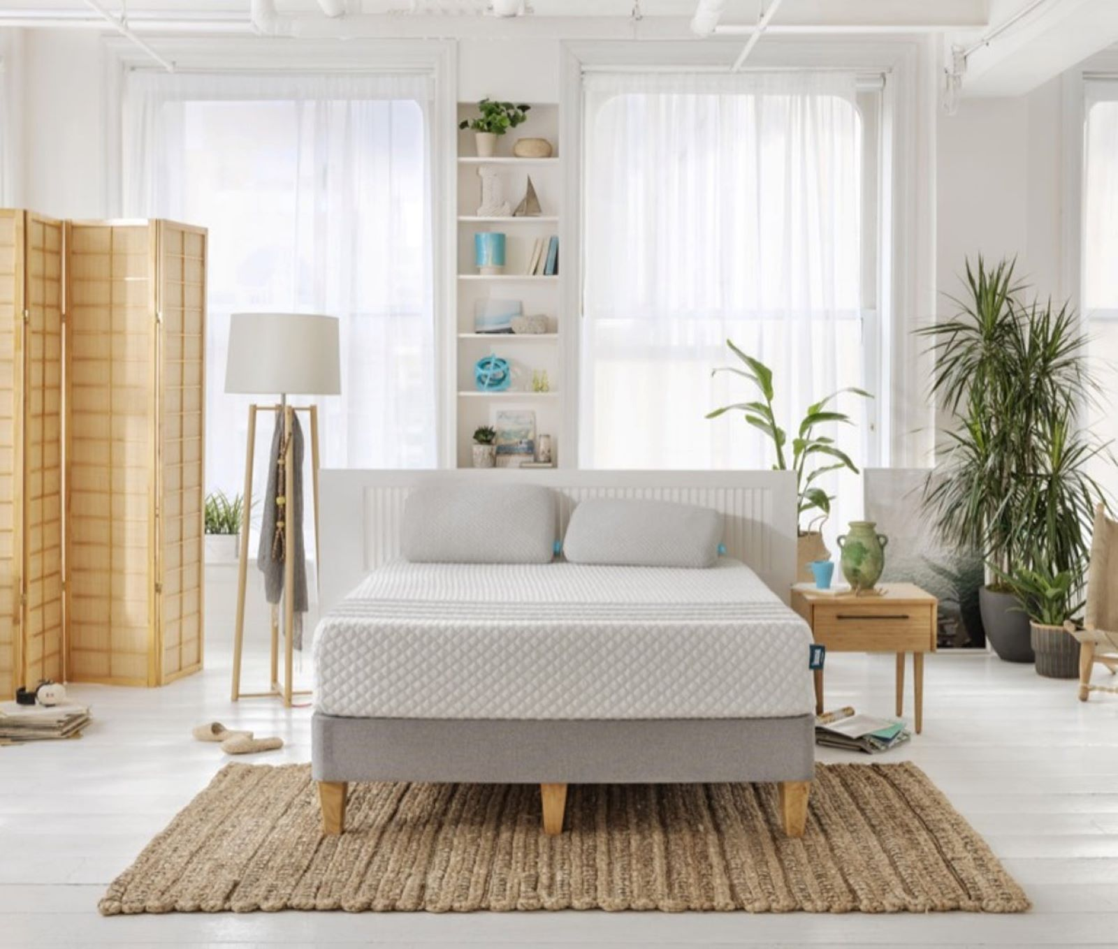 LESSA hybrid mattress in bedroom with white floors, walls and curtains. the bed is sitting on a brown rug