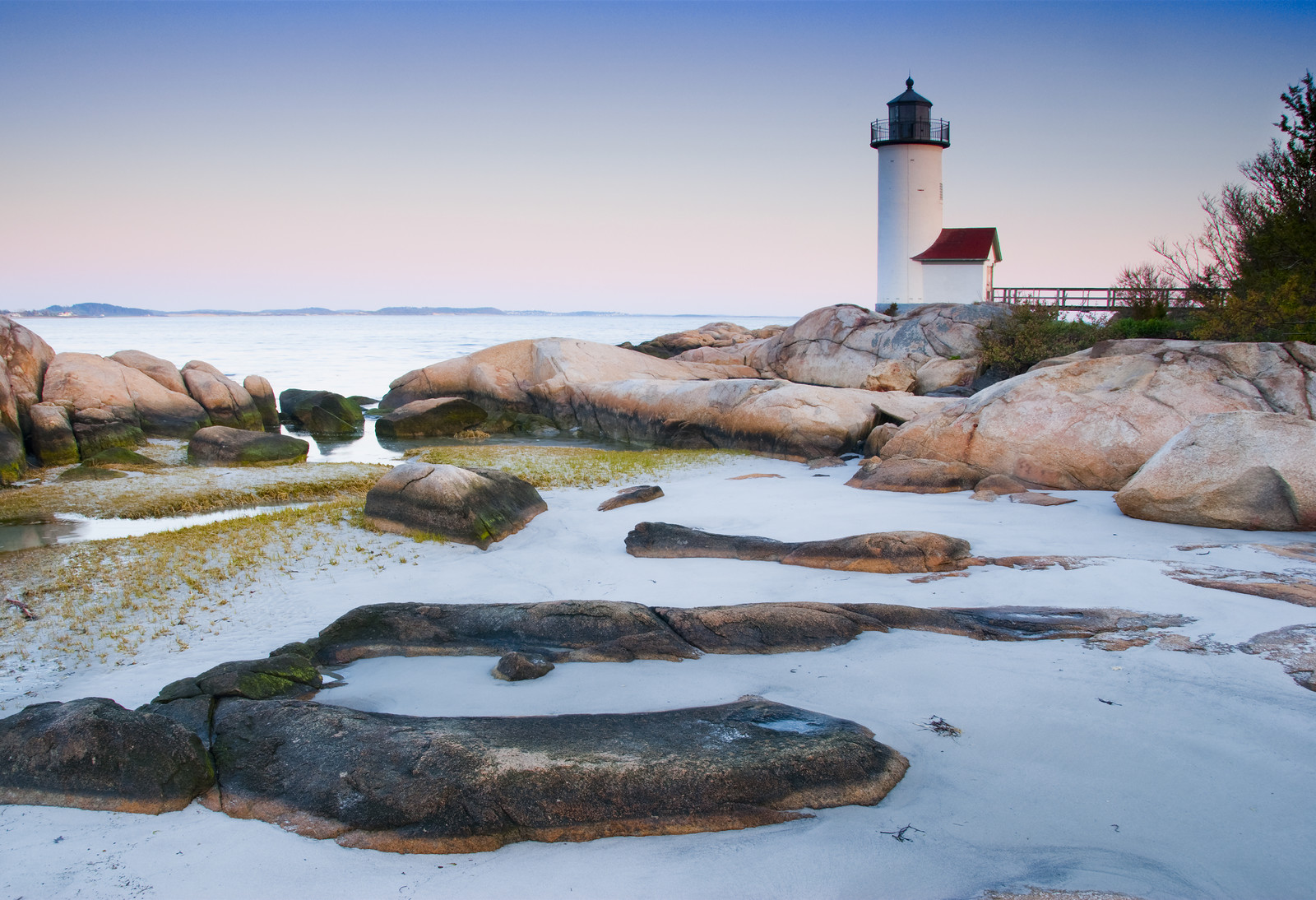 Light house on Atlantic Shore in Massachusetts from the rounded rocky shore at dawn