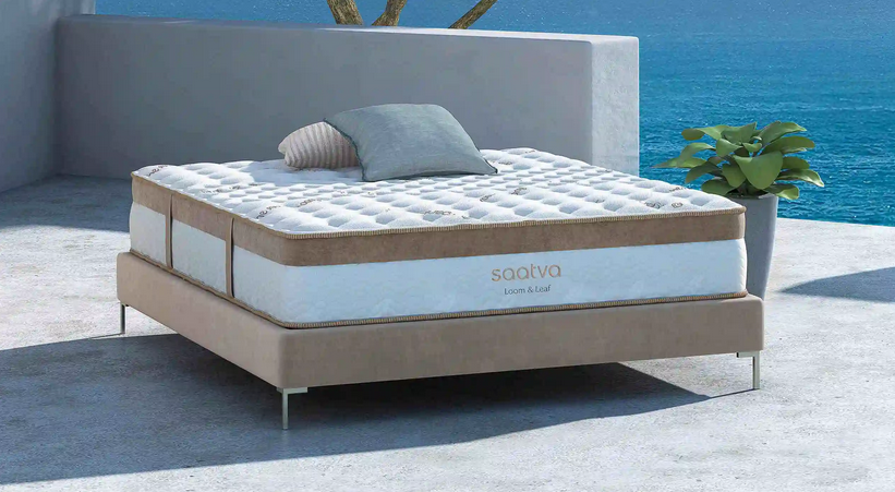 Saatva mattress sitting outside on a cement patio ojn a sunny day with the ocean in the backgound