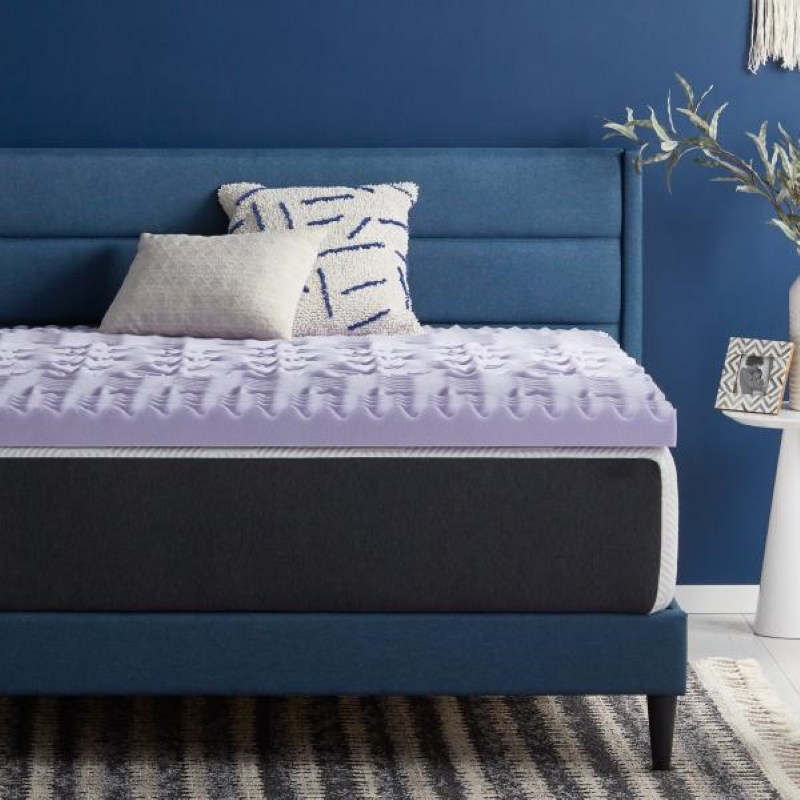 Lucid 5 zone lavender mattress topper sitting on a bed with a denim blue frame and cobolt blue walls