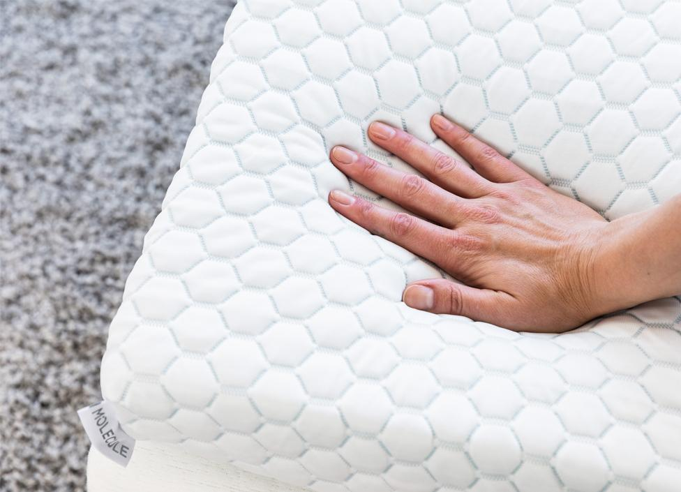 Molecule Air Tec mattress topper on a bed with a hand pressing down showing its plushness