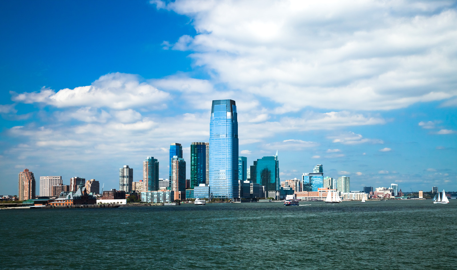 Top 5 Places To Retire in New Jersey - Photo of New Jersey Skyline across the Hudson river with blue skies white fluffy clouds with sailboats on the water