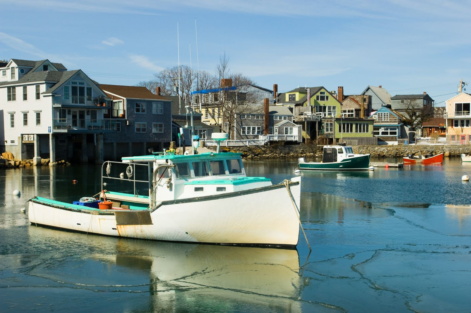 Rockport Massachusetts photo of boats on the water in early spring with blue skies and oceanside homes lining the shore