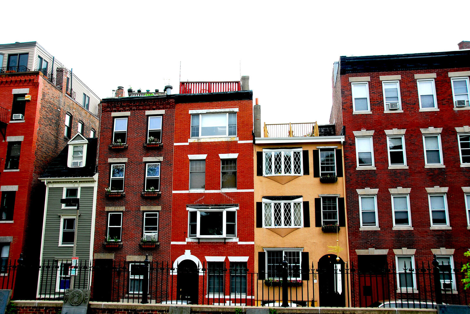 Colorful Row homes in north Boston with a iron fence  in the front