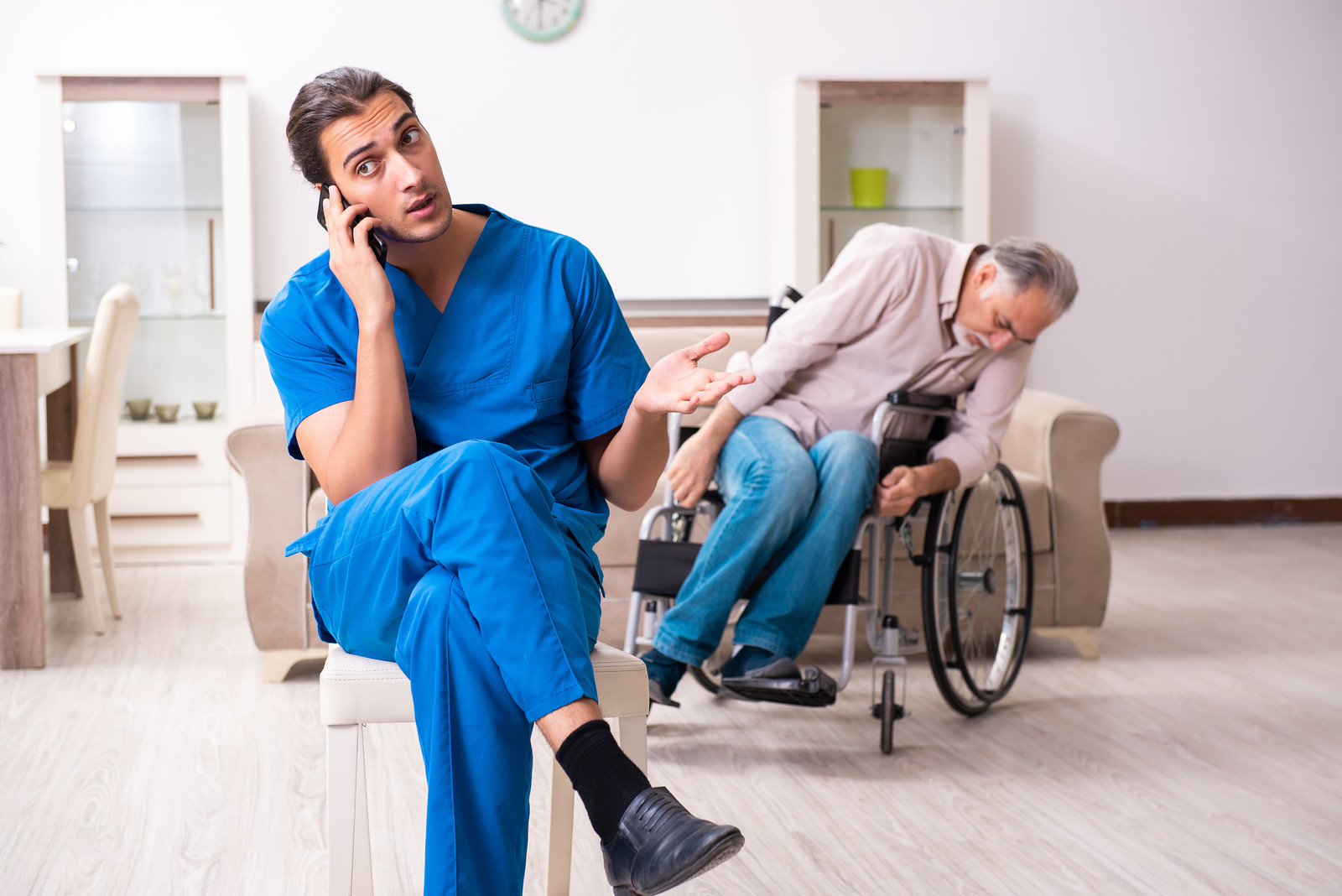 Senior man in wheelchair slumped over, male caregiver sitting in chair nearby on his cell phone ignoring the senior man in need