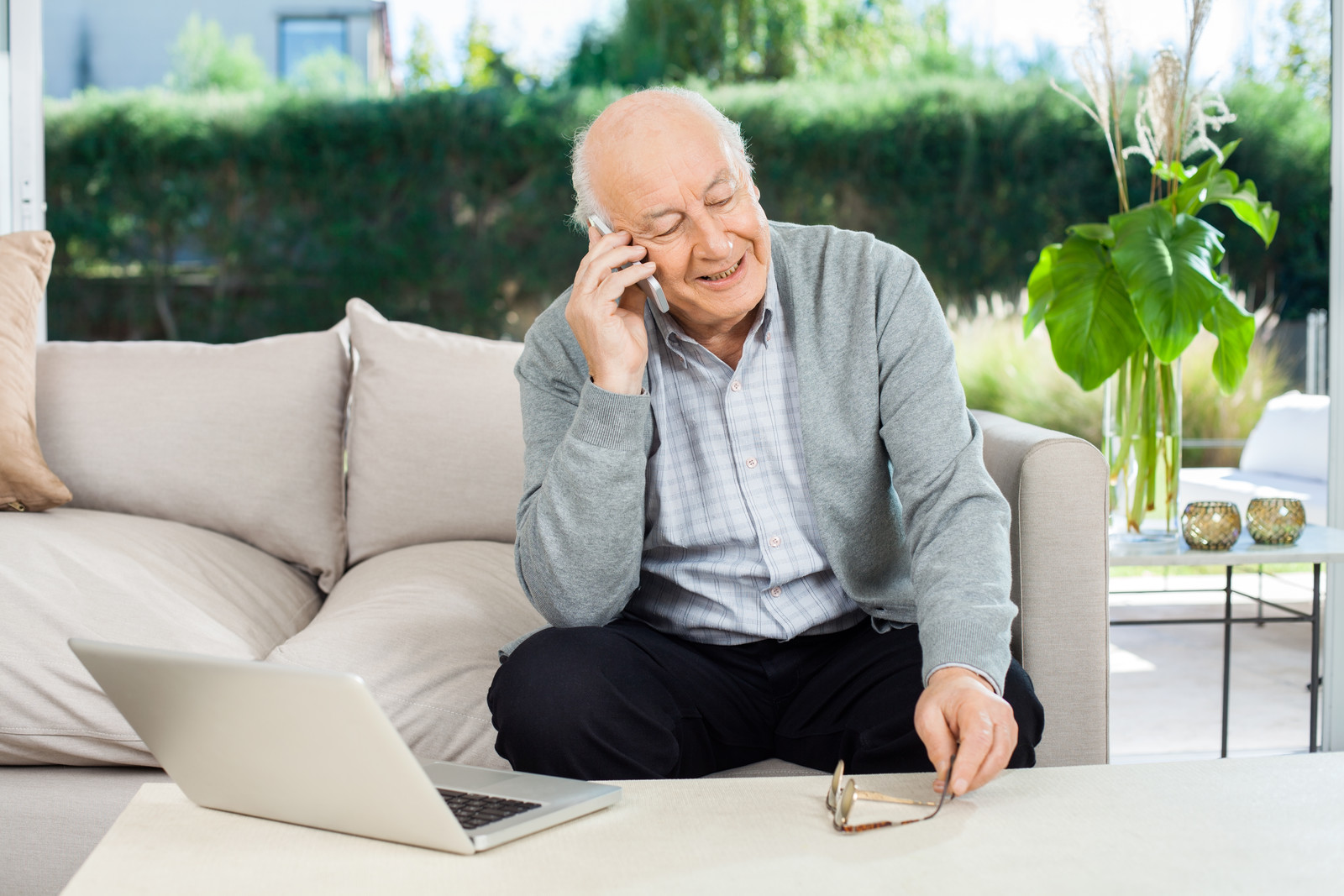 Senior man sitting on couch on an outdoor patio answering his smart phone in front of his lap top