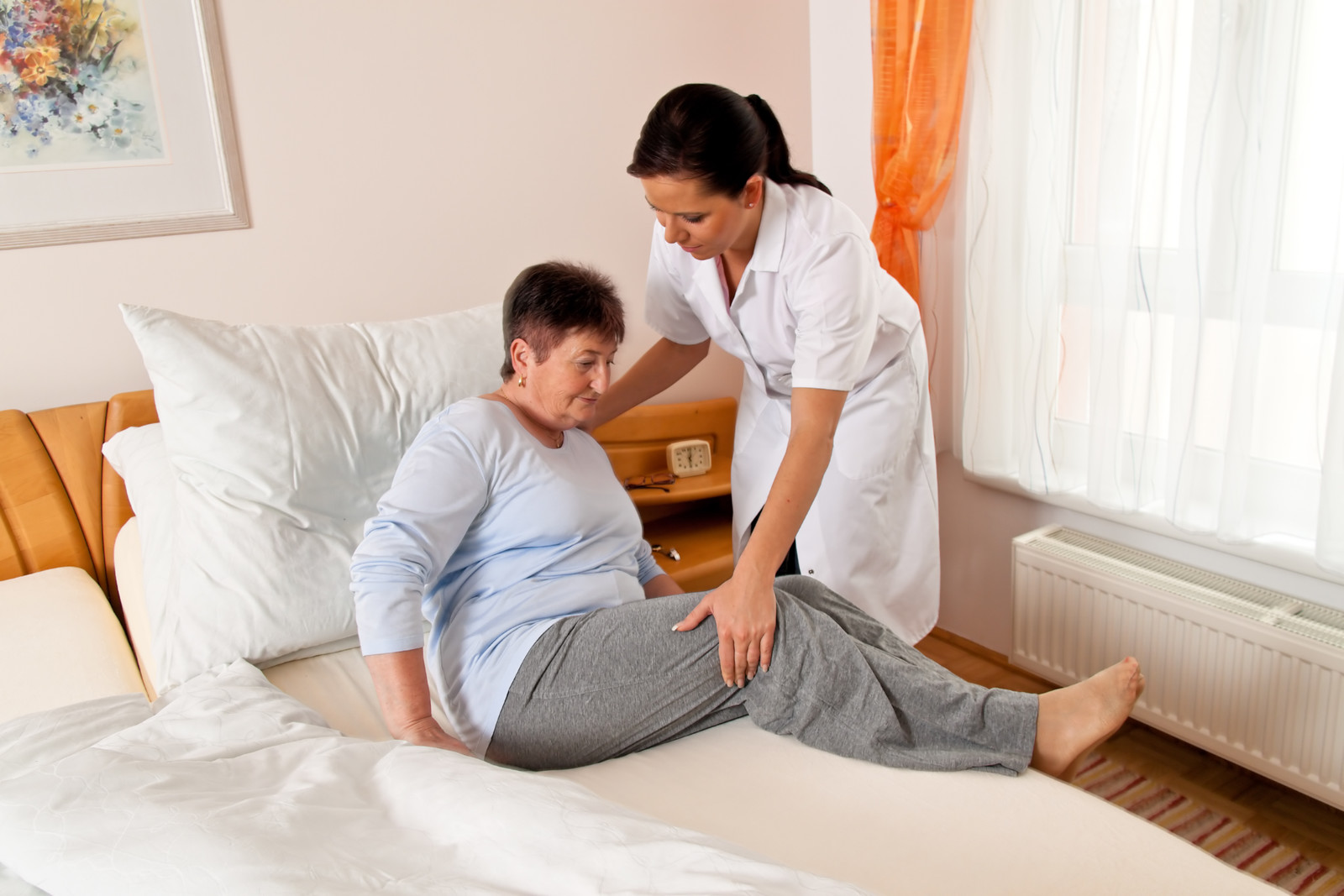 Senior woman being helped into bed by a nurse