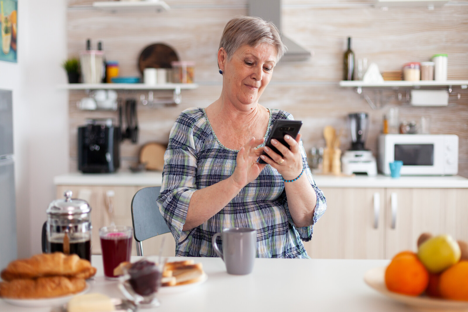 Senior woman sitting at kitchen counter at breakfast disconnecting call on cell phone