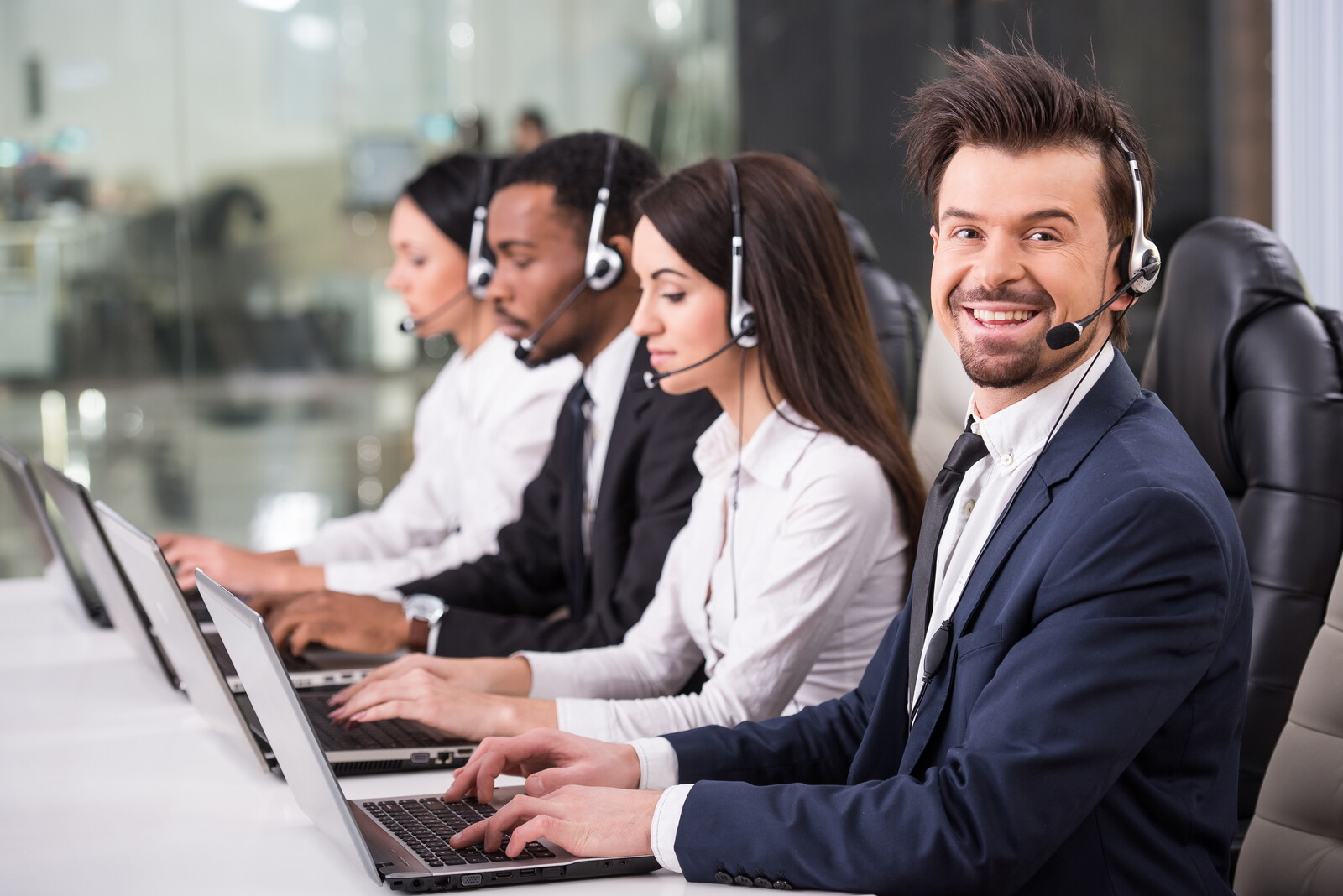 Side view of a line of telemarketing employees talking on headsets working on computers